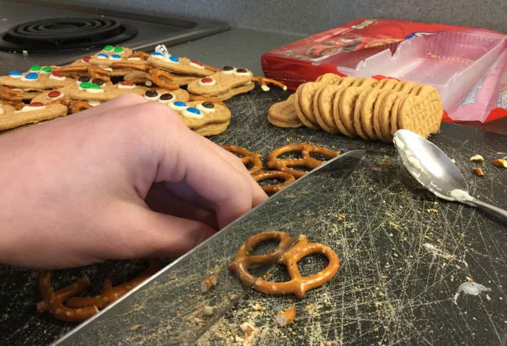 Breaking pretzels for Nutter Butter reindeer cookies