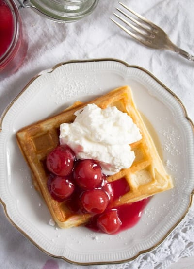 Belgian waffles with cherry sauce and whipped cream