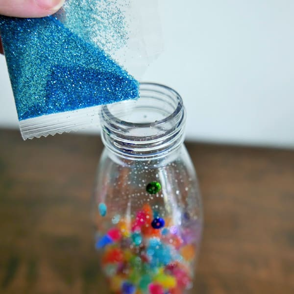 Add blue glitter to bottle
