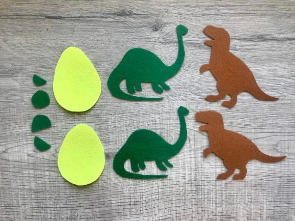 Cut out felt pieces of dinosaurs and eggs
