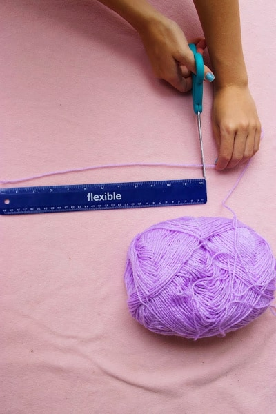 Measuring purple yarn with a ruler
