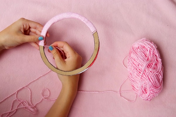 Wrapping light pink yarn around hoop