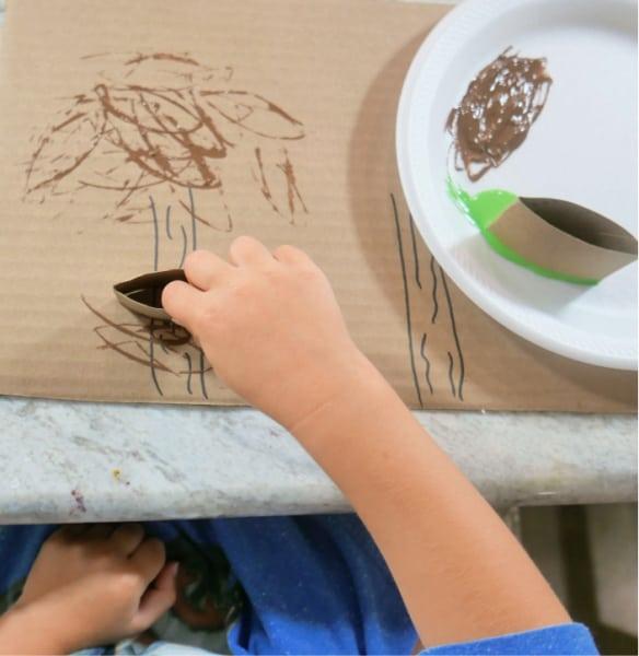 Dabbing brown paint on tree
