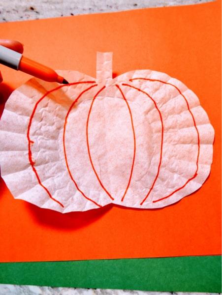 Draw on pumpkin with orange marker