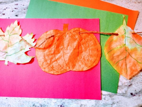 Stringing pumpkin and leaf garland